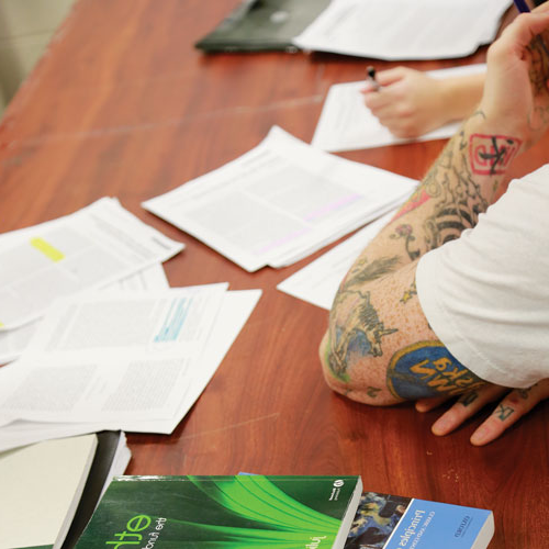 View of tattooed arm resting on desk with books